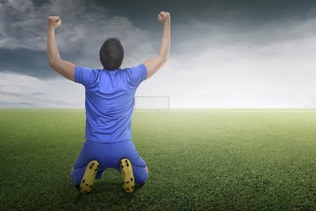 アジアのサッカー選手の男の背面図は彼の目標を祝う