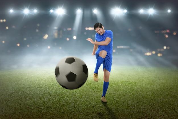 若いアジアのフットボール選手がボールを撃つ