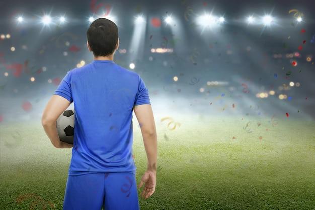 Вид сзади азиатского футболиста, стоящего с мячом