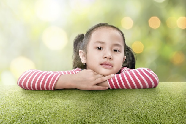 幸せなアジアの女の子は緑の芝生に寄りかかって