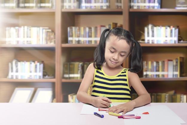 クレヨンで紙に描く幸せなアジア少女
