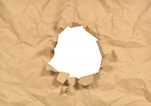 しわくちゃの紙の真ん中に引き裂かれた穴