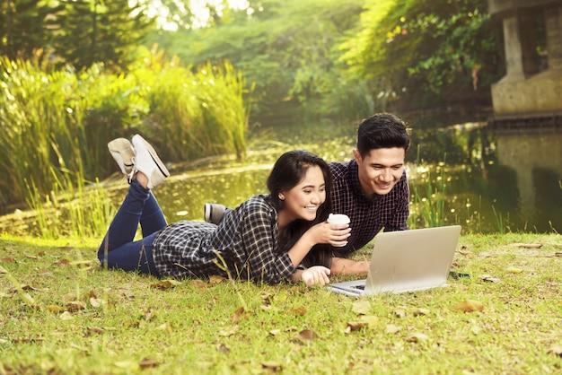 緑の芝生に横たわっている間ラップトップで映画を見て魅力的なアジアカップル