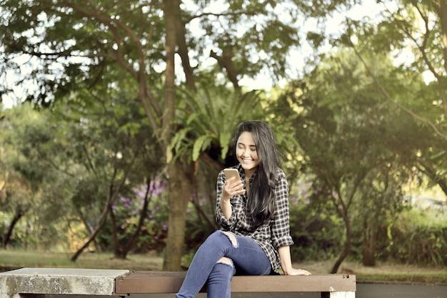 携帯電話の座っていると笑顔のアジアの女の子