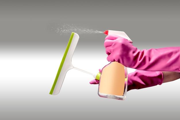 清掃用スプレーと清掃用具を使って手袋をはめる