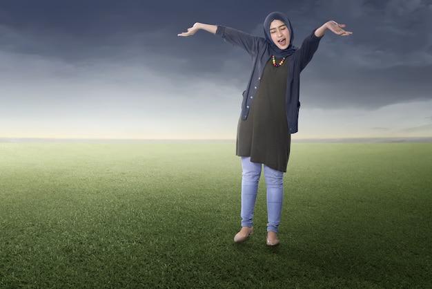 うれしそうなアジアのイスラム教徒の女性が立っています。