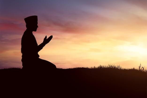 祈っているイスラム教徒の男性のシルエット