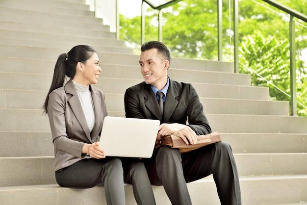 陽気なアジアのビジネス人々が外で作業計画について話し合う