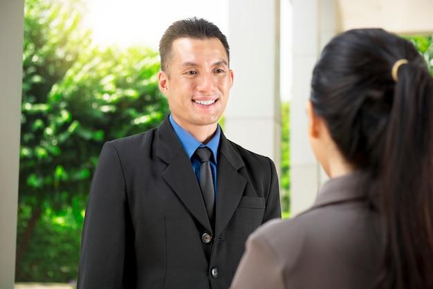 ハンサムなアジア系のビジネスマンが彼の同僚に事業計画について話し合う