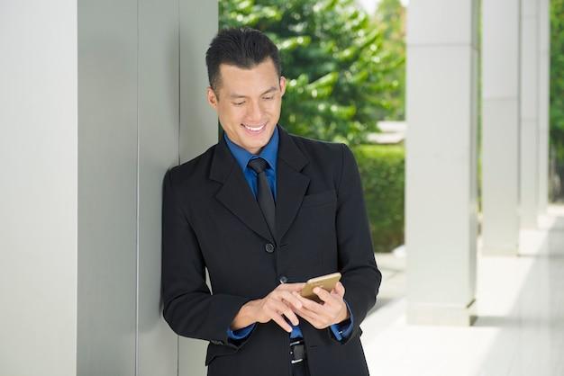 スマートフォンを使用してリラックスして若いアジア系のビジネスマン