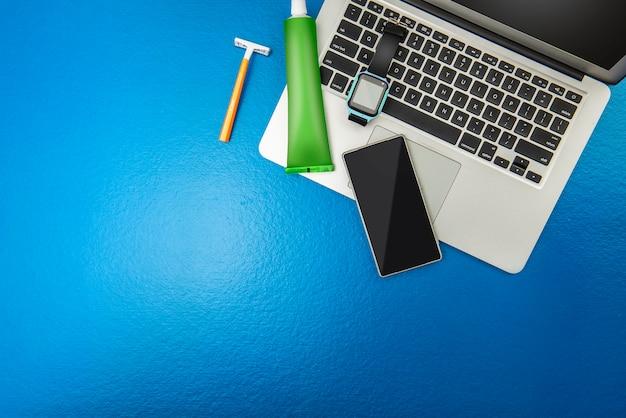Мужские вещи, такие как ноутбук, умные часы, мобильный телефон, желтая бритва и зубная паста для путешествий