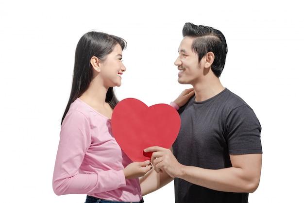 赤いハートを押しながらお互いを見ているアジアカップルの肖像画