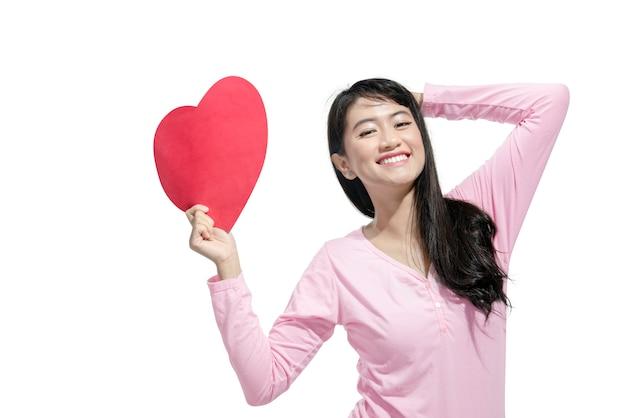 赤い紙のハートを持って幸せなアジア女