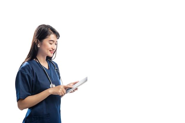 タブレットを使用して聴診器で笑顔のアジア医師女性
