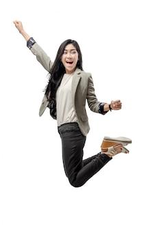 興奮してアジアビジネスの女性が腕を上げると空にジャンプ