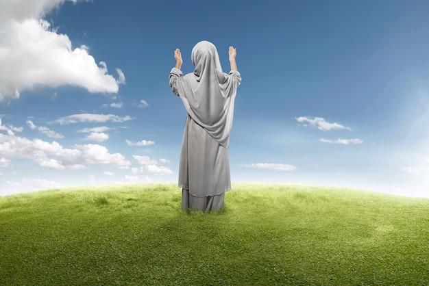アジアのイスラム教徒の少女が神に祈るの背面図