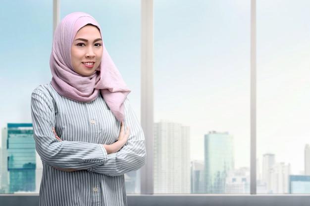 腕を組んで立っているかなりアジアのイスラム教徒の女性