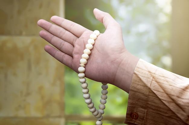 祈りビーズを保持しているイスラム教徒の男性