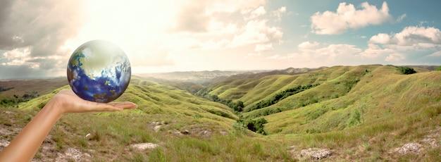 男性の手が風景の背景を持つ地球を保持