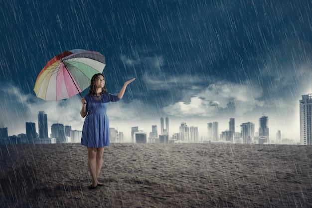 Счастливая азиатская женщина с зонтиком когда идет дождь