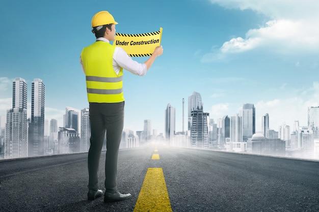 工事看板の下で保持しているアジアの建設労働者の背面図