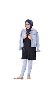 ジーンズのジャケットの立っていると笑顔のアジアのイスラム教徒の女性