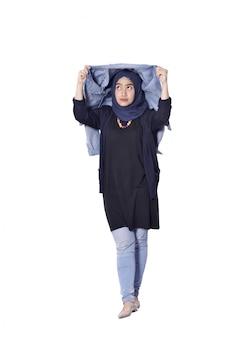 かなりのアジアのイスラム教徒の女性が彼女のジーンズのジャケットを使用して避難所を取る