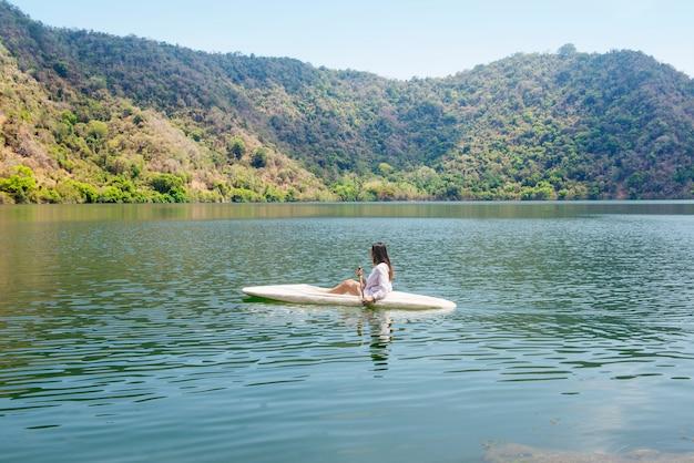 アジアの女性がサトンダ島の湖でカヤックを漕ぐ
