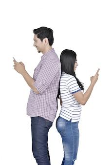 スマートフォンで背中合わせに立っている幸せなアジアカップル