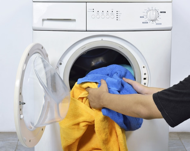Человек загружает грязные полотенца в стиральную машину для мытья