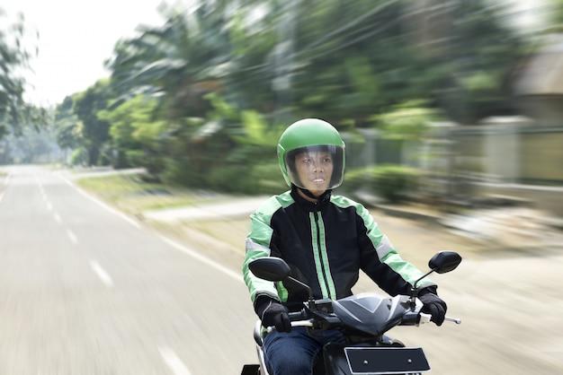 オートバイのタクシー運転手として働く若い男