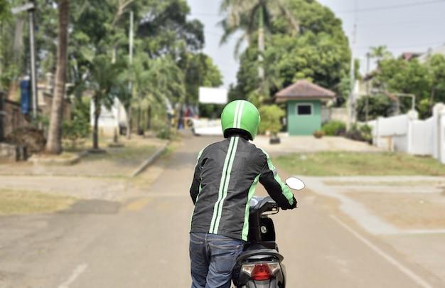 彼のオートバイを押すオートバイのタクシー運転手の後姿