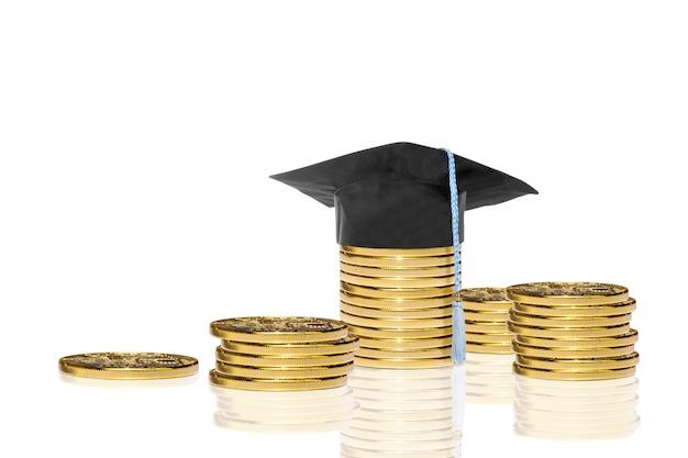 卒業の帽子と黄金のコインのスタック