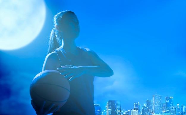Счастливая азиатская девушка держа баскетбол на ее руках с сценой ночи