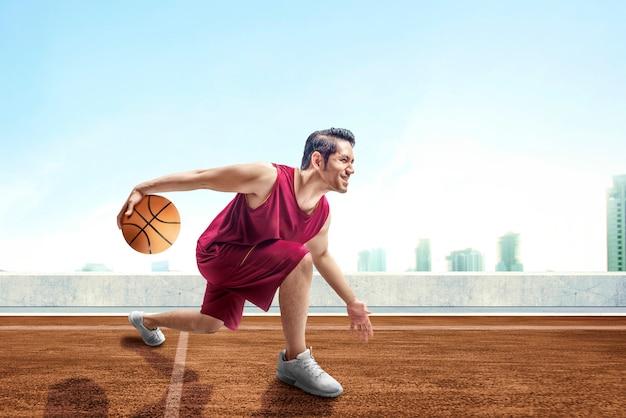 屋外のバスケットボールコートの足の間にボールをドリブルでポーズをとって若いアジア人男性バスケットボール選手