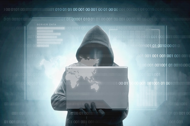 Хакер в черном балахоне держит ноутбук с виртуальным дисплеем данных сервера, гистограммой, двоичным кодом и картой мира