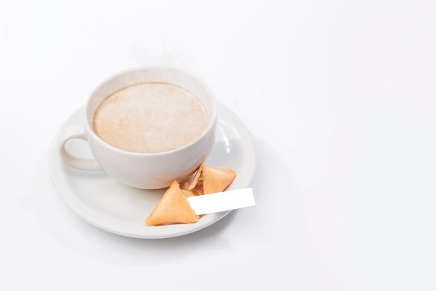 白紙の紙と一杯のコーヒーとフォーチュンクッキー