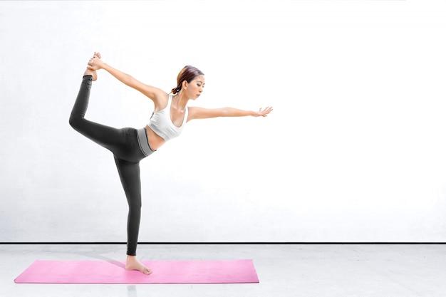 屋内でカーペットの上でヨガの練習アジアの健康な女性