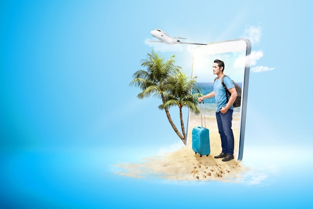 Азиатский мужчина с чемоданом и рюкзаком, стоя на пляже