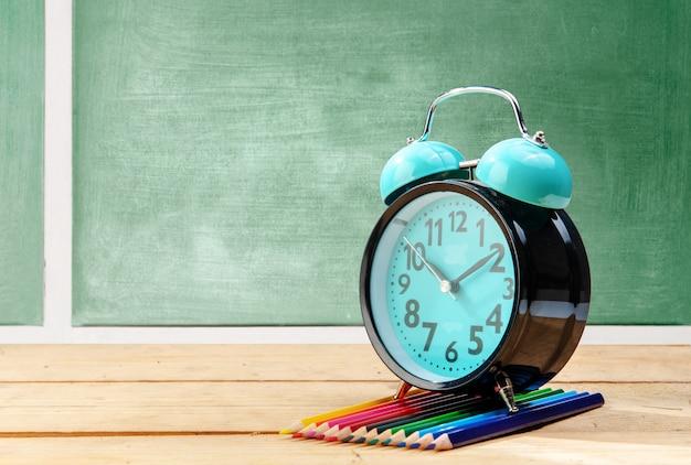 目覚まし時計と黒板と木製のテーブルの上の色鉛筆