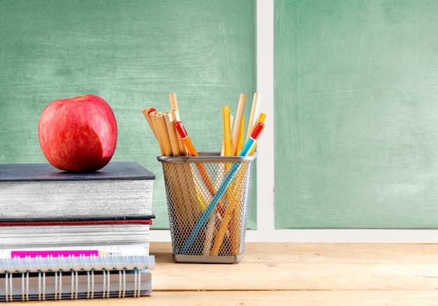 黒板と木製のテーブルの上のバスケットコンテナーにリンゴと鉛筆で本の山