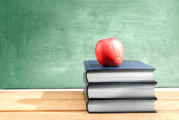 黒板と木製のテーブルの上のリンゴと本の山