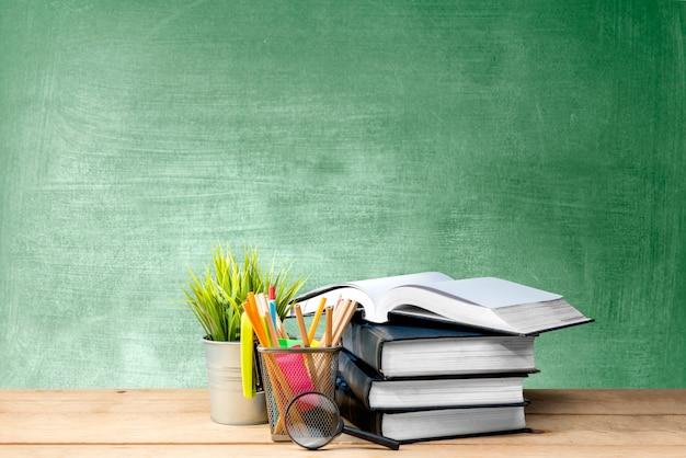 Стопка книг с растением в горшке и карандашами в корзине с увеличительным стеклом на деревянном столе