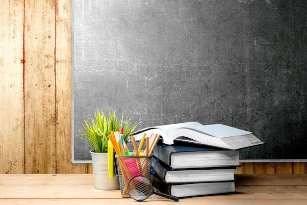 鉢植えの植物と木製のテーブルに虫眼鏡でバスケットコンテナーに鉛筆で本の山
