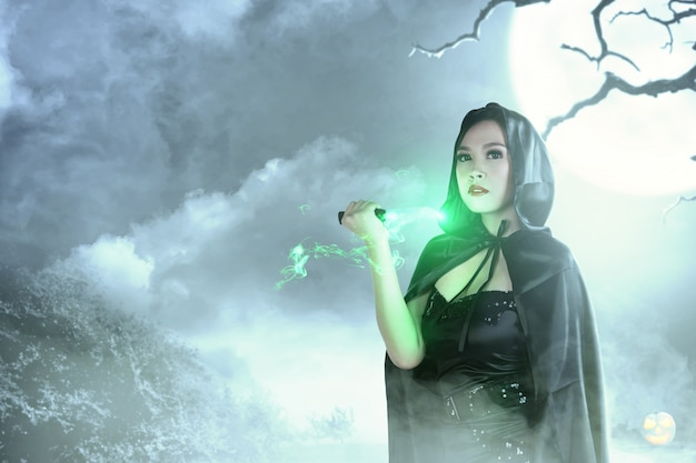 Азиатская ведьма в черном с капюшоном делает ритуал магии с ножом