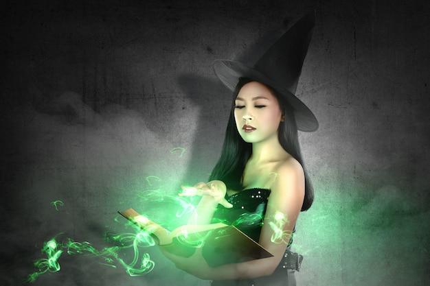 帽子のアジアの魔女女性は魔法の本から呪文を学ぶ