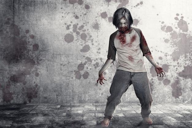 都市の通りを歩いて彼の体に血と傷の怖いゾンビ