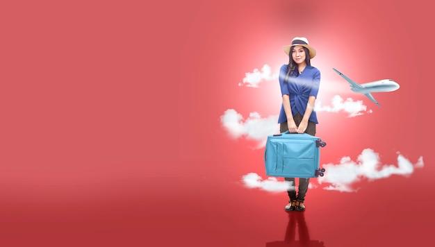 飛行機の背景と一緒に旅行に行くスーツケースバッグと帽子のアジアの女性
