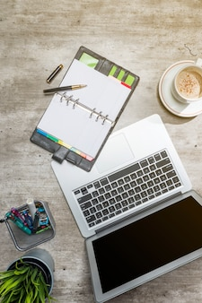 ノートパソコン、コーヒー、鉢植えの植物、ノートブック、ビジネスアクセサリーとビジネスデスクのトップビュー