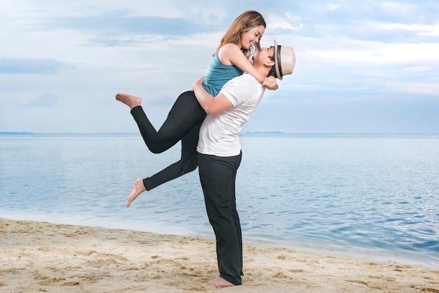 ビーチで彼のガールフレンドを抱き締める帽子で幸せなアジア男